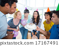 Business team blowing candles on a birthday cake 17167491