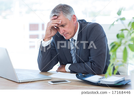 Stock Photo: Worried businessman with head in one hand