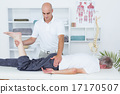 Physiotherapist doing leg massage to his patient 17170507