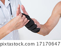 Doctor examining a man wrist 17170647