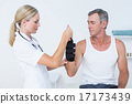 Doctor examining a man wrist 17173439