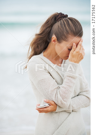 Stock Photo: Stressed young woman in sweater on beach with mobile phone