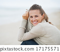 Portrait of happy young woman in sweater sitting on lonely beach 17175571