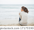 Young woman wrapping in sweater while sitting on lonely beach 17175590