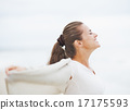 Happy young woman in sweater on lonely beach rejoicing 17175593
