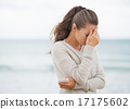 Stressed young woman in sweater on beach with cell phone 17175602
