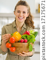 Portrait of smiling young woman with plate of fresh vegetables 17175671