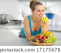 Happy young woman eating apple in modern kitchen 17175678
