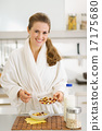 Happy young woman in bathrobe making healthy breakfast 17175680