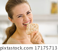 Happy young woman eating crisp bread 17175713