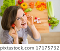 Smiling young woman using cherry tomatos as earring 17175732