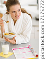 Thoughtful young woman in bathrobe eating breakfast in kitchen 17175772