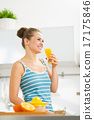 Happy young woman drinking fresh orange juice 17175846