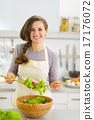 Happy young housewife mixing vegetable salad 17176072
