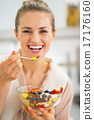 Smiling young woman eating fresh fruit salad 17176160