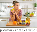 Portrait of thoughtful young housewife with fruits in modern kit 17176173