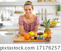 Portrait of young housewife with fruits in modern kitchen 17176257