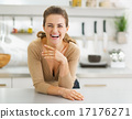 Portrait of smiling young housewife in modern kitchen 17176271
