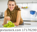 Happy young housewife eating grape 17176290