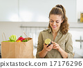 Young housewife exploring purchasings after shopping in kitchen 17176296