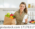 Smiling young housewife with check and shopping bag full of vege 17176317