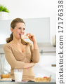 Young woman eating crisp bread in kitchen 17176338