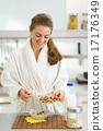 Happy young woman having healthy breakfast in kitchen 17176349