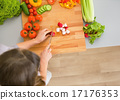 Young housewife cutting vegetables 17176353
