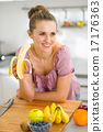 Young woman eating banana in kitchen 17176363