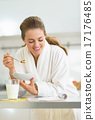 Happy young woman having healthy breakfast in kitchen 17176485