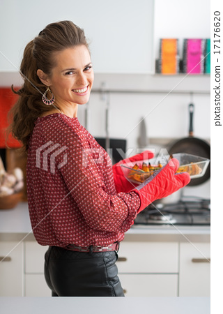 Portrait of happy young housewife holding baked pumpkin 17176620