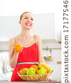 Happy young woman with fruits in kitchen 17177546