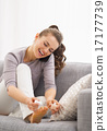 Happy young woman applying nail polish while talking cell phone 17177739