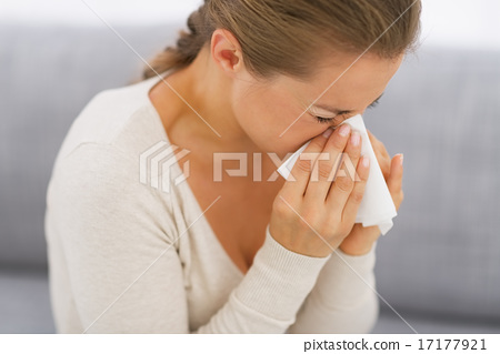 Stock Photo: Young woman sitting on couch and blowing nose