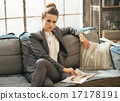 Business woman sitting on sofa in loft apartment and looking mag 17178191