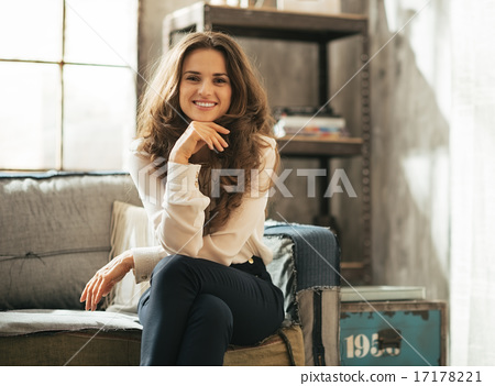 Happy young woman sitting in loft apartment 17178221