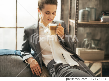 Portrait of happy business woman drinking coffee latte in loft a 17178224