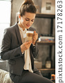 Portrait of happy business woman drinking coffee latte in loft a 17178263