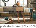 Thoughtful young woman with dslr photo camera using laptop in lo 17178270