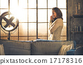 Young woman talking mobile phone in loft apartment 17178316