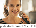 Portrait of happy young woman singing with microphone 17178318