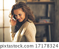Portrait of young woman talking cell phone in loft apartment 17178324