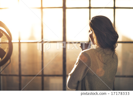 Stock Photo: Young woman enjoying cup of coffee in loft apartment. rear view