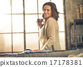 Happy young woman enjoying cup of coffee in loft apartment 17178381