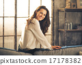 Elegant woman sitting on back of sofa smiling over shoulder 17178382