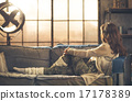 Woman in casual clothing sitting on sofa looking out 17178389