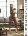 Full length portrait of young woman singing karaoke in loft apar 17178420
