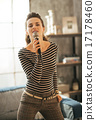 Young woman singing with microphone in loft apartment 17178460