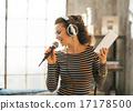 Happy young woman singing karaoke in loft apartment 17178500