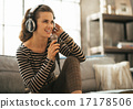 Portrait of happy young woman singing with microphone in loft ap 17178506